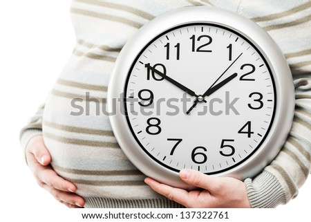 Pregnancy and new life concept - beauty pregnant woman hand holding large office wall clock showing time - stock photo