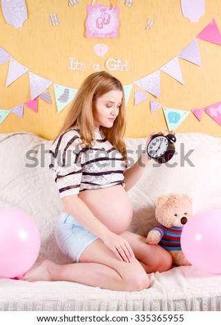 Pregnancy concept. happy pregnant woman with an alarm clock on the sofa at home. - stock photo