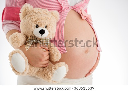 Pregnancy concept. Pregnant woman holding teddy bear toy in his hand, studio isolated - stock photo