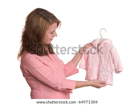 Pregnancy concept without showing abdomen - pregnant woman pick clothing for her unborn daughter - stock photo
