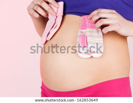 pregnancy, maternity and health concept - belly of a pregnant woman with two pairs of baby mittens - stock photo