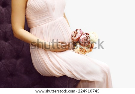 Pregnancy, motherhood and happy future mother concept - pregnant woman and bouquet flowers sitting on armchair - stock photo
