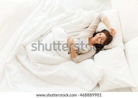 pregnancy, rest, people and expectation concept - happy pregnant woman lying in bed at home bedroom