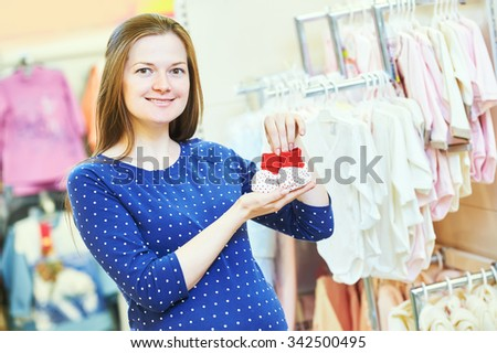Pregnancy shopping. Portrait of young pregnant woman choosing newborn clothes at baby shop store - stock photo