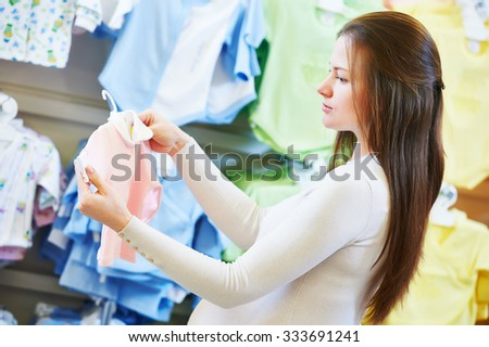Pregnancy shopping. Young pregnant woman choosing newborn clothes at baby shop store - stock photo