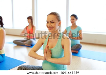 pregnancy, sport, fitness, people and healthy lifestyle concept - group of happy pregnant women exercising in lotus pose at gym yoga