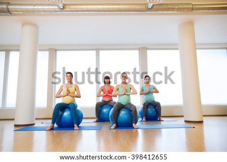pregnancy, sport, fitness, people and healthy lifestyle concept - group of happy pregnant women exercising on ball in gym - stock photo