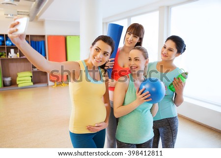 pregnancy, sport, fitness, people and healthy lifestyle concept - group of happy pregnant women with sports stuff taking selfie by smartphone in gym - stock photo