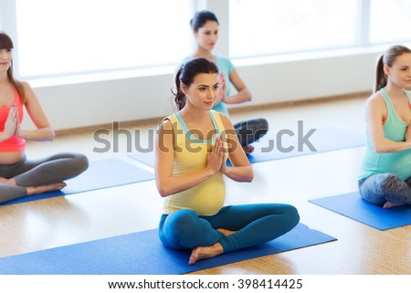 pregnancy, sport, fitness, people and healthy lifestyle concept - group of happy pregnant women exercising yoga in lotus pose in gym