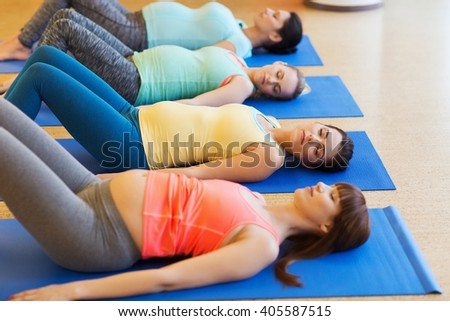 pregnancy, sport, fitness, people and healthy lifestyle concept - group of happy pregnant women exercising on mats in gym - stock photo