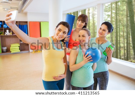 pregnancy, sport, fitness, people and healthy lifestyle concept - group of happy pregnant women with sports stuff taking selfie by smartphone in gym over natural window view background - stock photo