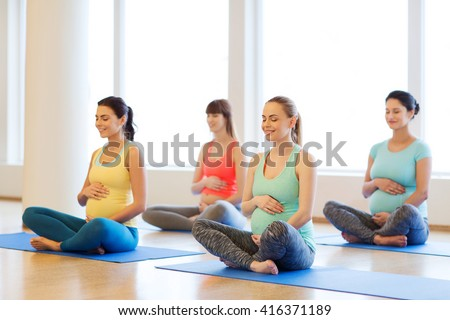 pregnancy, sport, fitness, people and healthy lifestyle concept - group of happy pregnant women exercising yoga and and meditating in lotus pose in gym - stock photo