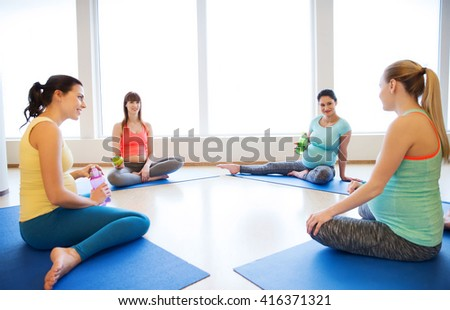 pregnancy, sport, fitness, people and healthy lifestyle concept - group of happy pregnant women with water bottles sitting on mats and talking in gym - stock photo