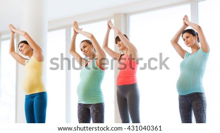 pregnancy, sport, fitness, people and healthy lifestyle concept - group of happy pregnant women exercising in gym - stock photo