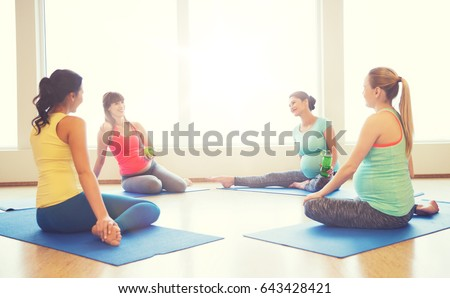 pregnancy, sport, fitness, people and healthy lifestyle concept - group of happy pregnant women with water bottles sitting on mats and talking in gym