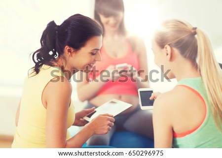 pregnancy, sport, fitness, people and healthy lifestyle concept - group of happy pregnant women with tablet pc computer and smartphone sitting on balls in gym