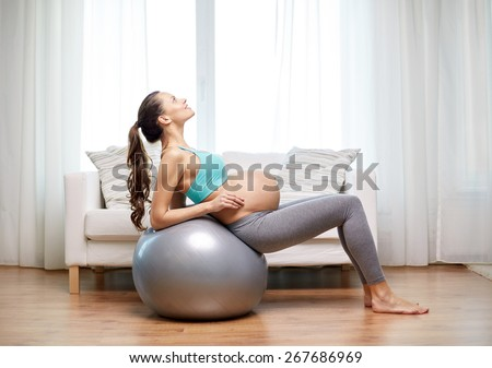 pregnancy, sport, fitness, people and healthy lifestyle concept - happy pregnant woman exercising on fitball at home - stock photo