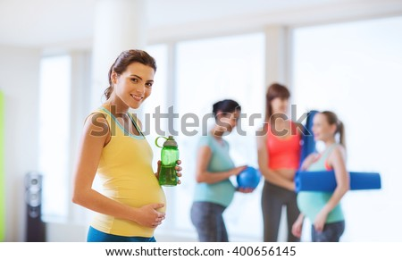 pregnancy, sport, fitness, people and healthy lifestyle concept - happy pregnant woman with water bottle in gym - stock photo