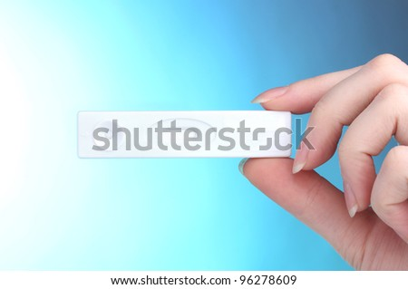 pregnancy test in hand on blue background - stock photo