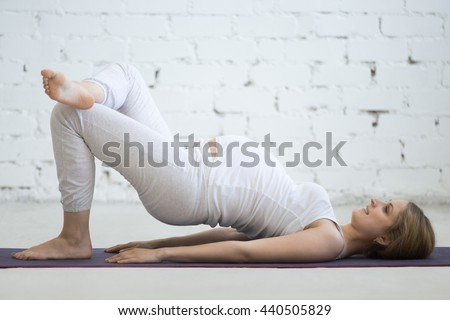 Pregnancy Yoga and Fitness concept. Beautiful young pregnant yoga model working out indoor. Pregnant happy fitness person practicing yoga at home. Prenatal one legged variation of shoulder bridge pose - stock photo