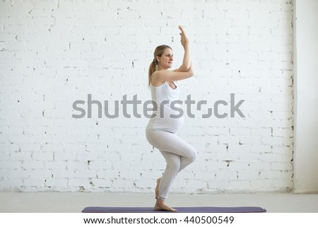 Pregnancy Yoga and Fitness concept. Portrait of beautiful young pregnant yoga model working out indoor. Pregnant happy fitness person enjoying yoga practice at home. Prenatal Eagle Pose, Garudasana - stock photo