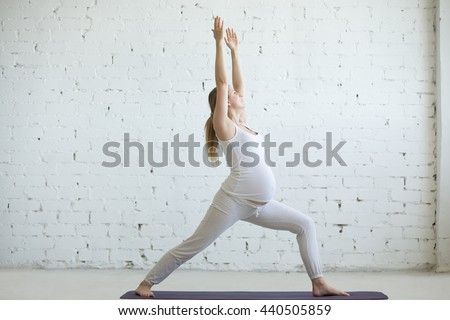 Pregnancy Yoga and Fitness concept. Portrait of beautiful young pregnant yoga model working out indoor. Pregnant happy fitness person enjoying yoga practice at home. Prenatal Warrior I posture - stock photo