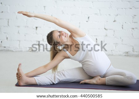 Pregnancy Yoga and Fitness concept. Portrait of young pregnant yoga model working out indoors. Pregnant smiling fitness person practicing yoga at home. Prenatal Side bend in Janu Sirsasana pose - stock photo