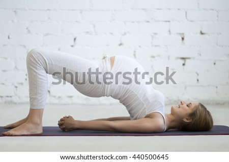 Pregnancy Yoga and Fitness concept. Portrait of young pregnant yoga model working out indoors. Pregnant happy fitness person enjoy yoga practice at home. Prenatal shoulder bridge exercise. Full length - stock photo