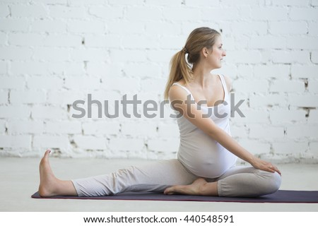 Pregnancy Yoga and Fitness concept. Portrait of young pregnant yoga model working out indoors. Pregnant fitness person practicing yoga at home. Prenatal gentle spinal twist in Janu Sirsasana pose - stock photo