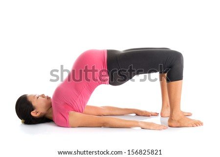 Pregnancy yoga class. Full length healthy Asian pregnant woman doing yoga exercise stretching, full body isolated on white background. Yoga bridge pose. - stock photo