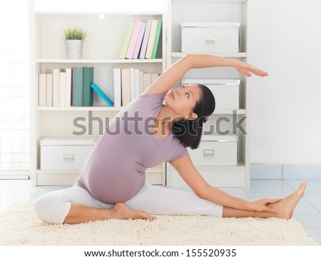 Pregnancy yoga meditation. Full length healthy 8 months pregnant calm Asian woman meditating or doing yoga exercise at home. Relaxation yoga sitting side stretch positions. - stock photo