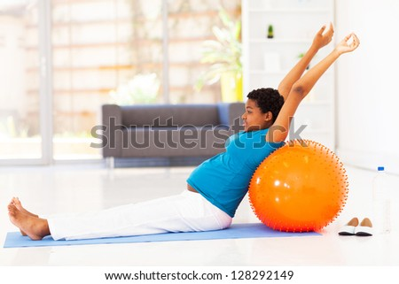 pregnant african american woman exercising on floor at home - stock photo