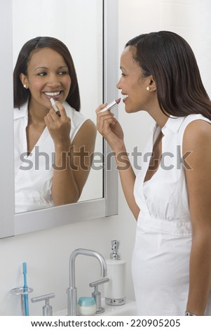Pregnant African woman applying lipstick in mirror - stock photo