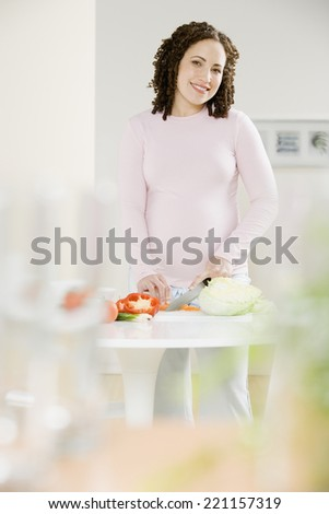 Pregnant African woman chopping vegetables - stock photo