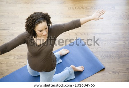 Pregnant African woman practicing yoga - stock photo