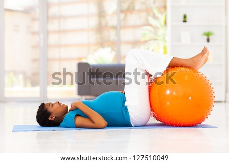 pregnant african woman workout on exercise mat at home - stock photo