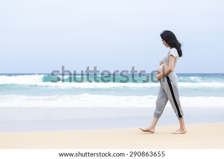 Pregnant beach walking female relaxing