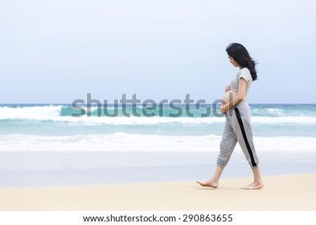 Pregnant beach walking female relaxing - stock photo