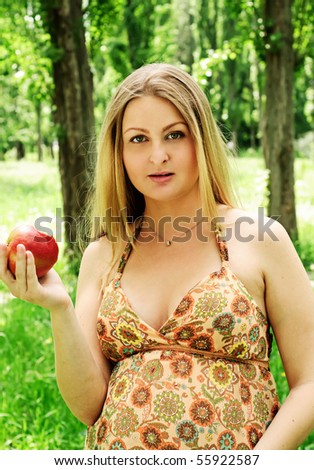 Pregnant beautiful woman with apple