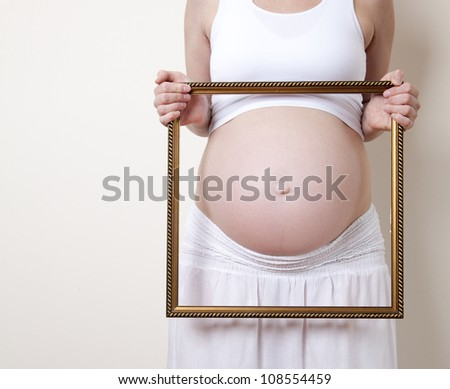 Pregnant Belly with a picture frame - stock photo