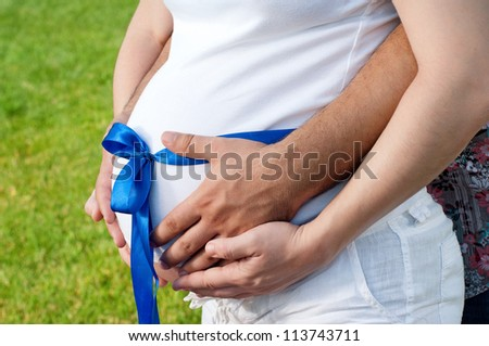 Pregnant belly with blue ribbon. Third trimester. - stock photo