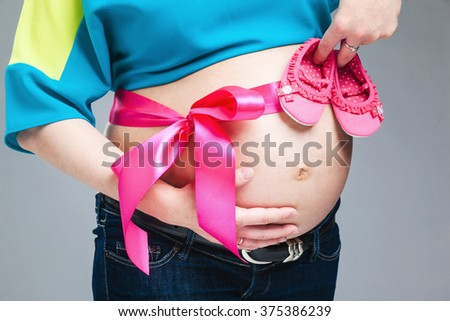 Pregnant belly with pink ribbon. Third trimester. - stock photo