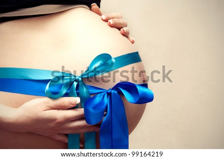 Pregnant belly with two blue ribbons - stock photo