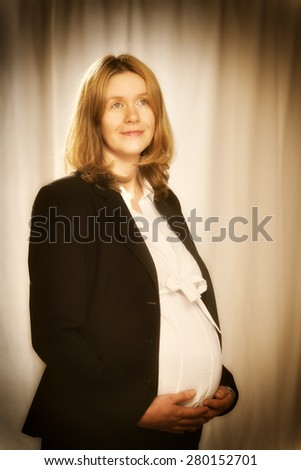 Pregnant blond business woman in black business clothing - stock photo