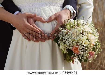 Pregnant Bride With Groom Creating Heart Shape On Her Tummy - stock photo