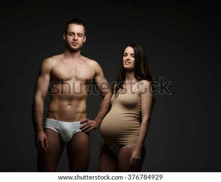 Pregnant brunette woman and shirtless athletic man posing over  dark background.