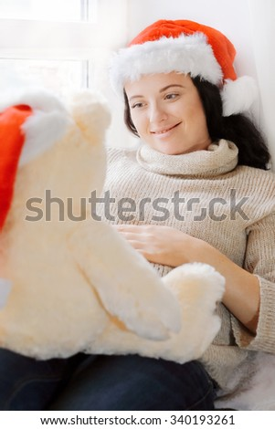 Pregnant brunette woman relaxing near window and playing with toy bear wearing Santa s hat