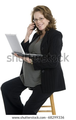 pregnant business woman in her forties, holding cell phone and laptop, glasses, sitting, wearing black suit, isolated on white - stock photo
