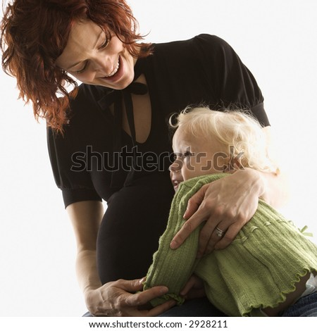 Pregnant Caucasian mid-adult woman hugging her daughter.