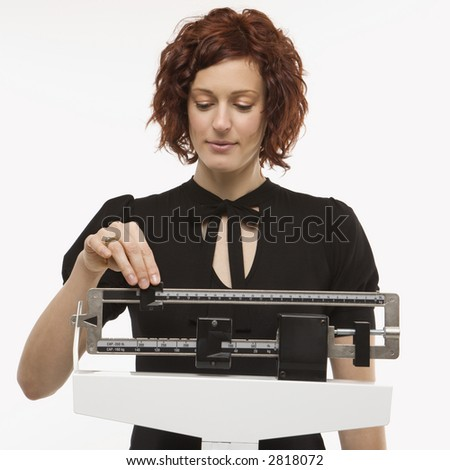 Pregnant Caucasian mid-adult woman reading her weight on scale.